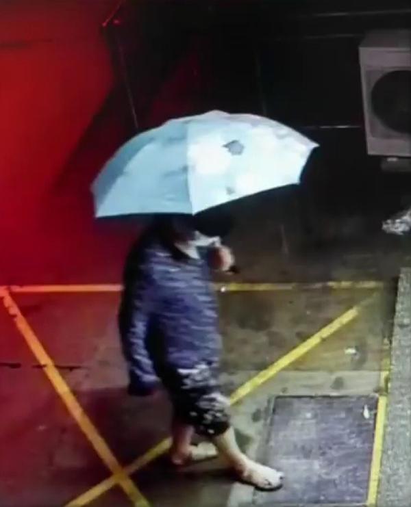 Nghi phạm đeo khẩu trang, dùng ô che kín mặt đi rút tiền. Ảnh: CCTV.