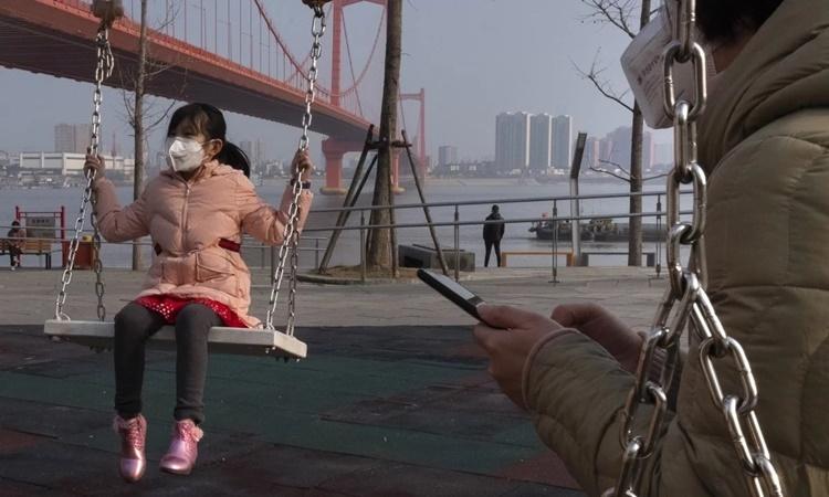 Một bé gái đeo khẩu trang chơi xích đu bên sông Dương Tử ở Vũ Hán. Ảnh: AP.