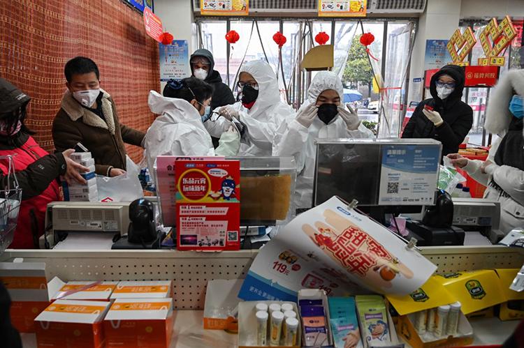 Cảnh mọi người tấp nập mua khẩu trang ở một hiệu thuốc tại Vũ Hán hôm 25/1. Ảnh: AFP