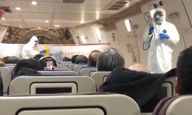 Tiếp viên trên chuyến bay rời Vũ Hán trong trang phục bảo hộ. Ảnh: New York Times.
