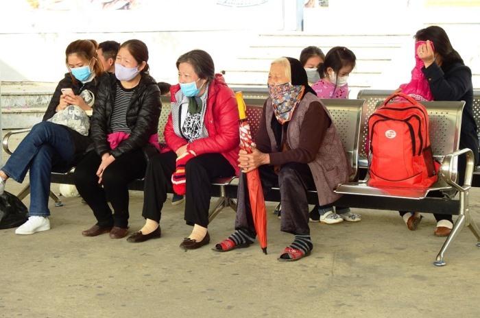 Một đoàn khách nội địa đeo khẩu trang ngồi nghỉ tại cảng. Ảnh: Minh Cương