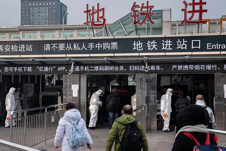 Các nhân viên an ninh mặc đồ bảo hộ kiểm tra thân nhiệt của hành khách tại lối vào một ga tàu điện ngầm ở Bắc Kinh hôm 27/1. Ảnh: AFP.