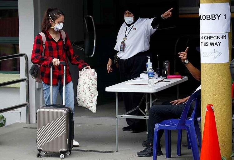 Sinh viên trở về từ Trung Quốc được đưa tới khu cách ly trong đại học Nanyang, Singapore, hôm 28/1. Ảnh: Reuters.