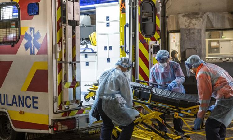 Ba nhân viên y tế khiêng xe đẩy cứu thương tại bệnh viện Queen Mary, Hong Kong hôm 29/1. Ảnh: Bloomberg.