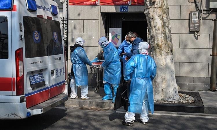 Nhân viên y tế mặc đồ bảo hộ đưa nạn nhân nghi nhiễm viêm phổi ra khỏi căn hộ ở Vũ Hán, Hồ Bắc hôm 30/1. Ảnh: AFP.