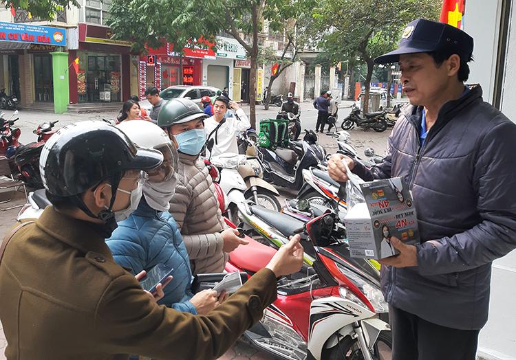 Người dân kéo đến nhận khẩu trang miễn phí trên phố Chùa Láng. Ảnh: Phạm Nga.