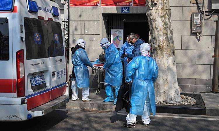 Nhân viên y tế đưa bệnh nhân từ nhà vào viện ở Vũ Hán ngày 30/1. Ảnh: AFP.