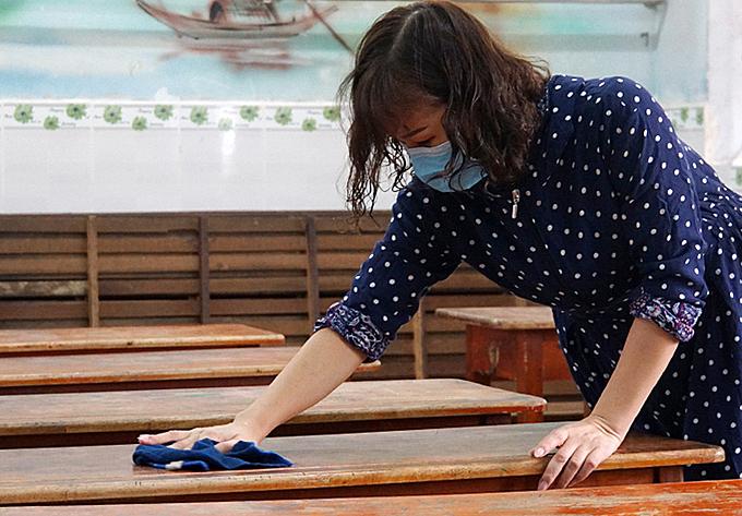 Giáo viên trường Tiểu học Nguyễn Thị Minh Khai (quận Gò Vấp) vệ sinh, khử khuẩn phòng học ngày 2/2. Ảnh: Mạnh Tùng.