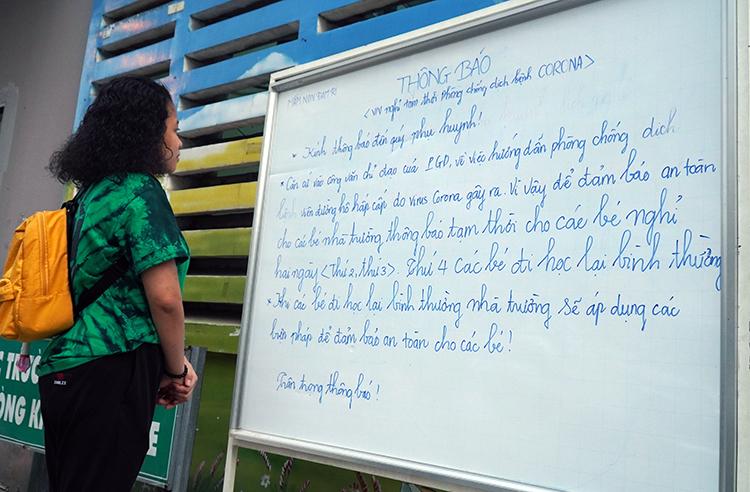 Phụ huynh xem thông báo của trường mầm non ĐamRi, TP Biên Hòacho học sinh nghỉ họcngày 3-4/2 để chống dịch, chiều 2/2. Ảnh: Phước Tuấn.