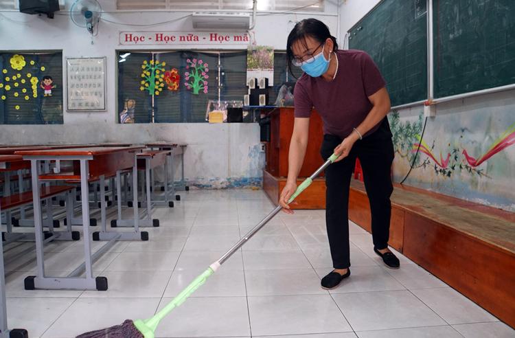 Giáo viên trường Tiểu học Nguyễn Thị Minh Khai (quận Gò Vấp) vệ sinh, khử khuẩn phòng học để đón học sinh trở lại vào sáng mai 3/2. Ảnh: Mạnh Tùng