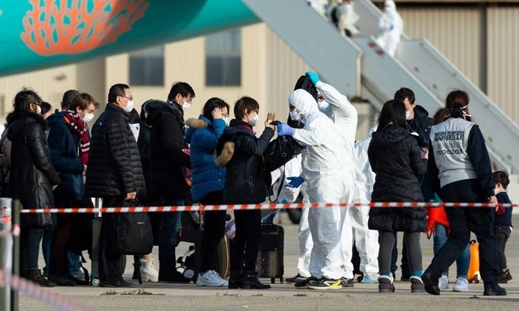 Các hành khách được kiểm tra trước khi rời chuyến bay sơ tán từ Trung Quốc tới Pháp ngày 2/2. Ảnh: AFP.