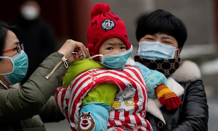Một phụ nữ đeo khẩu trang cho con trên đường phố Bắc Kinh, Trung Quốc hôm 2/2. Ảnh: AFP.
