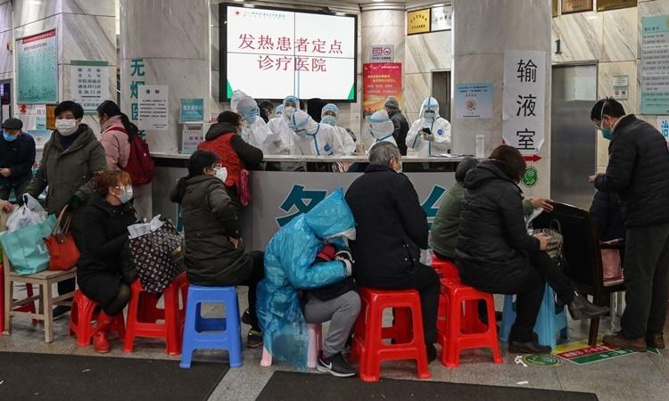 Người dân xếp hàng chờ giúp đỡ tại bệnh viện ở Vũ Hán. Ảnh: AFP.