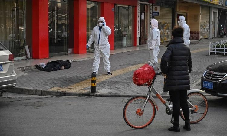 Một người đàn ông chết trên đường phố Vũ Hán hôm 30/1 song chưa rõ có phải do nhiễm nCoV hay không. Ảnh: AFP.