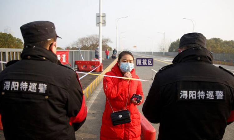 Người phụ nữ đến từ Hồ Bắc bị nhân viên an ninh kiểm tra trên cầusông Cửu Giang, thành phố Cửu Giang, tỉnh Giang Tây hôm 31/1. Ảnh: Reuters.