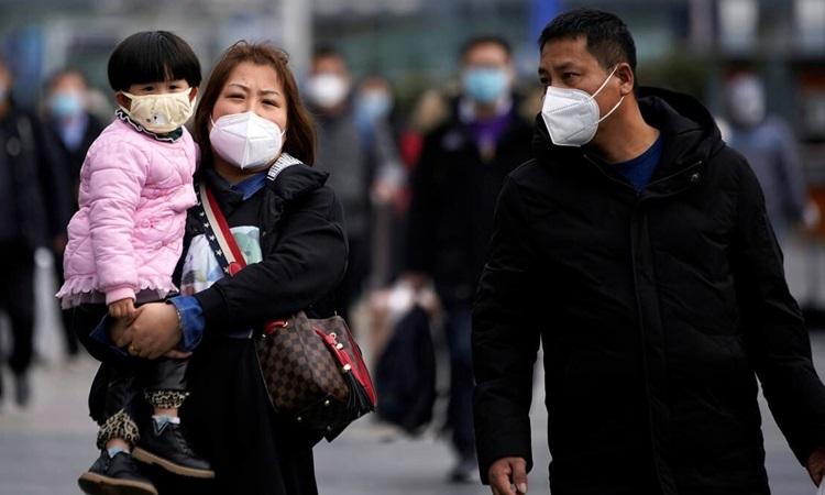 Hành khách đeo khẩu trang bên ngoài nhà ga Thượng Hải hôm 3/2. Ảnh: Reuters.