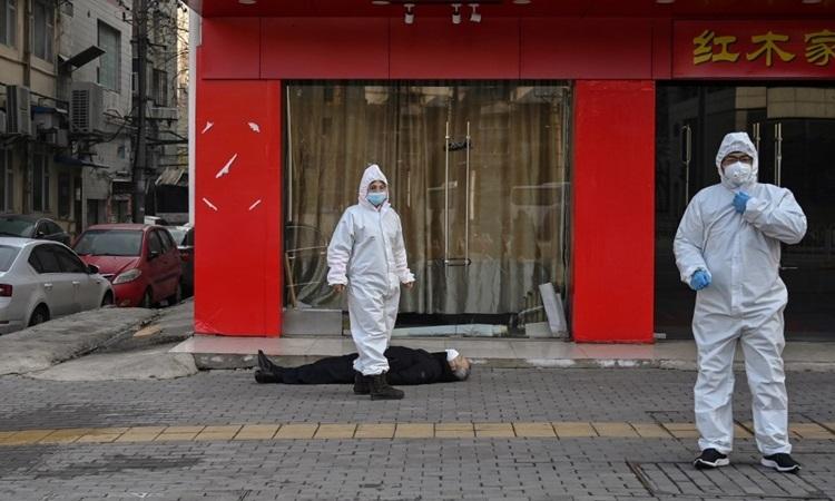 Chuyên gia y tế Trung Quốc tại hiện trường người đàn ông lớn tuổi chết trên vỉa hè Vũ Hán hôm 30/1. Ảnh: AFP.