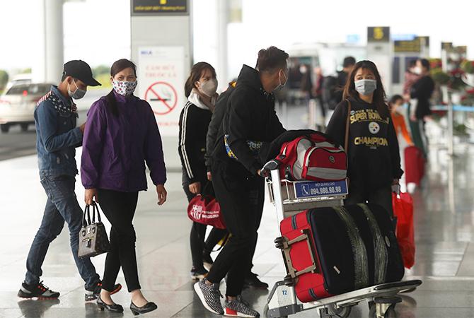Phần lớn hành khách đến sân bay Nội Bài đeo khẩu trang. Ảnh: Gia Chính.