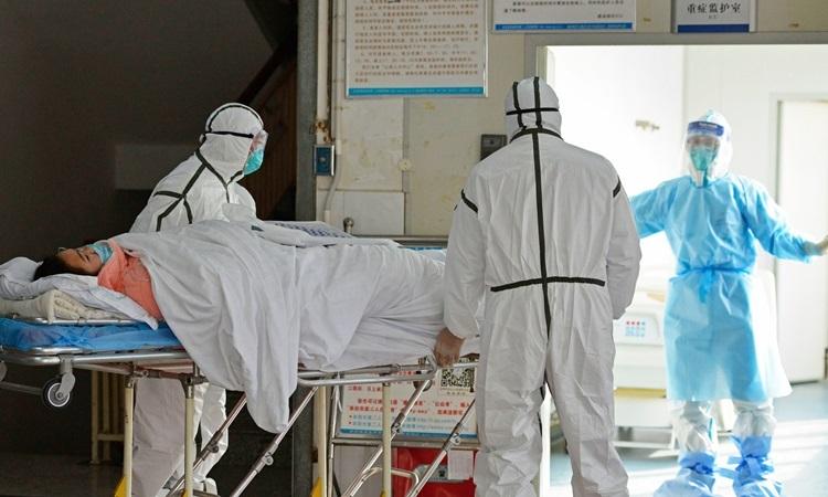 Các bác sĩ chuyển bệnh nhân nhiễm nCoV vào khu vực cách ly ở bệnh viện thành phố Phụ Dương, tỉnh An Huy hôm 1/2. Ảnh: AP.