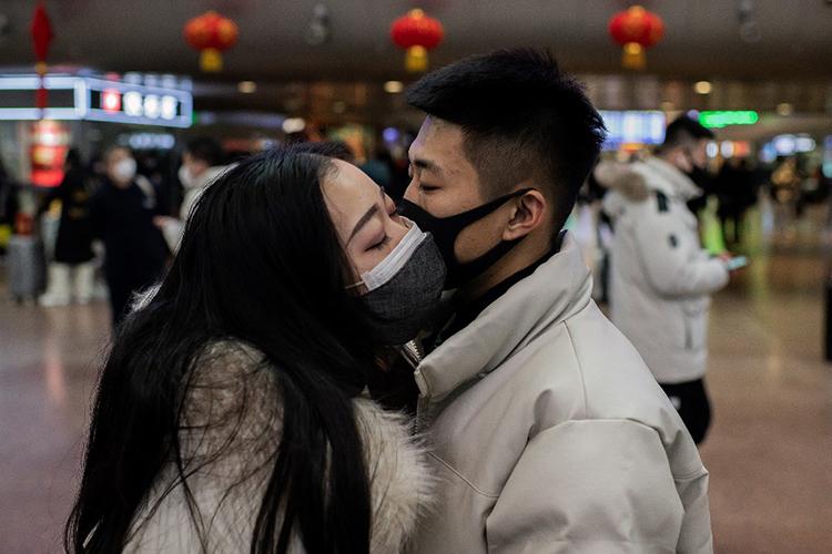 Một đôi nam nữ đeo khẩu trang hôn tạm biệt khi về nghỉ Tết ở ga Bắc Kinh, Trung Quốc hôm 24/1. Ảnh: AFP
