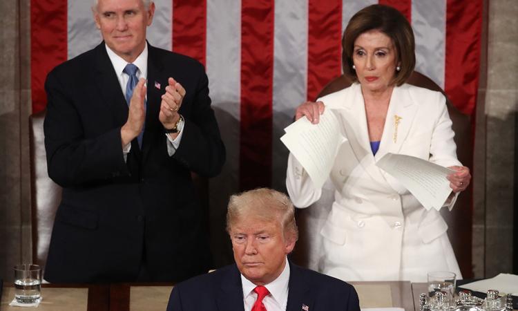 Chủ tịch Hạ viện Nancy Pelosi (áo trắng) xé bản sao Thông điệp Liên bang 2020 của Trump. Ảnh: AFP.