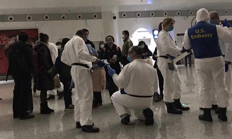 Nhân viên đại sứ quán Mỹ kiểm tra sức khỏe cho người sơ tán ở sân bay Vũ Hán, tỉnh Hồ Bắc hôm 5/2. Ảnh: Washington Post.