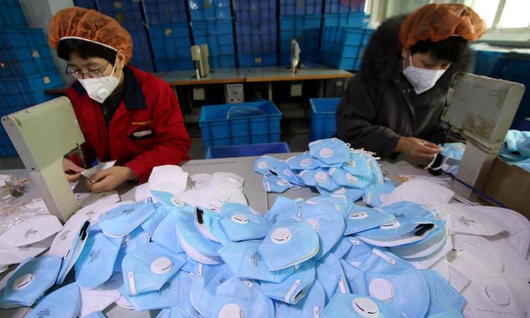 Các công nhân sản xuất khẩu trang tại một nhà máy ở Hàm Đan, tỉnh Hà Bắc, Trung Quốc hôm 22/1. Ảnh: Reuters.