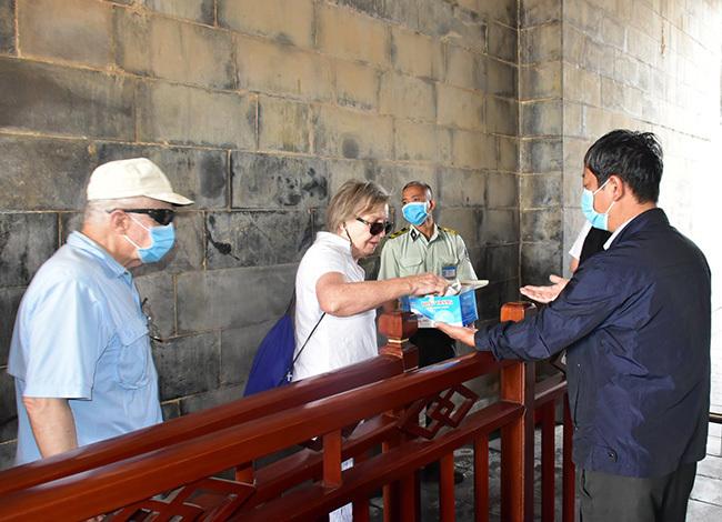 Du khách vào tham quan Đại nội Huế được phát khẩu trang miễn phí. Ảnh: Võ Thạnh