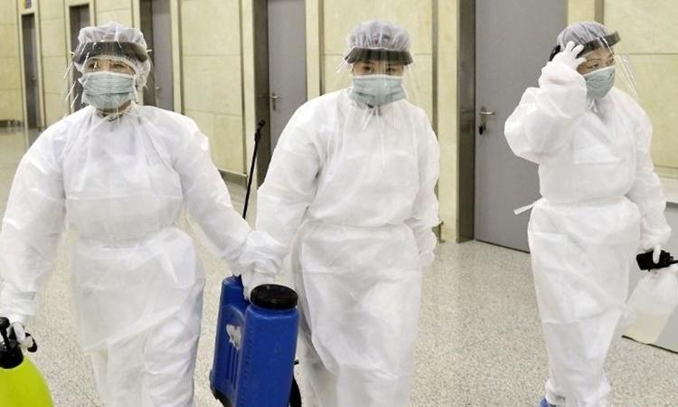 Các nhân viên y tế Triều Tiên trong đồ bảo hộ tại sân bay quốc tế Bình Nhưỡng ngày 1/2. Ảnh: Kyodo News.