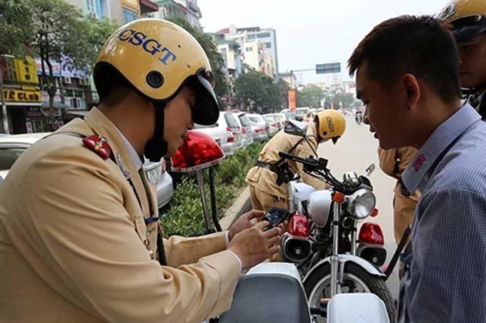 CSGT Hà Nội cho tài xế ôtô xem hình ảnh vi phạm giao thông bị camera ghi lại, để xử phạt, tháng 8/2019.Ảnh: Bá Đô.