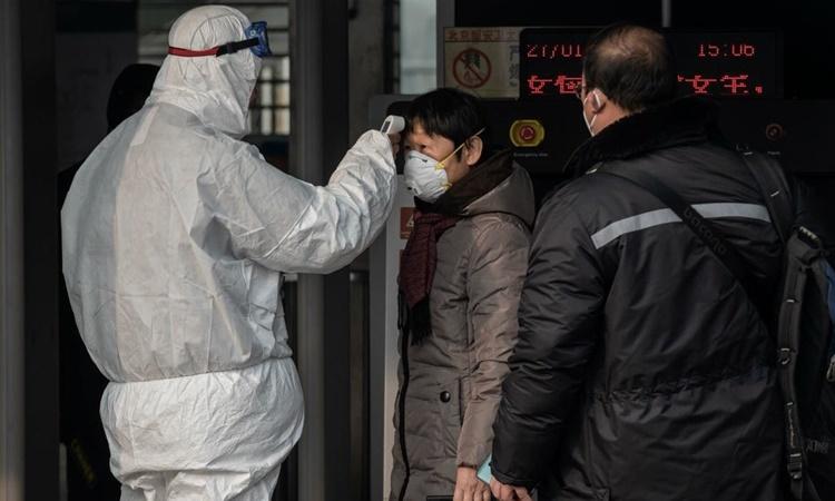 Nhân viên an ninh kiểm tra nhiệt độ của hành khách đi tàu điện ngầm ở Bắc Kinh ngày 27/1. Ảnh: Reuters.