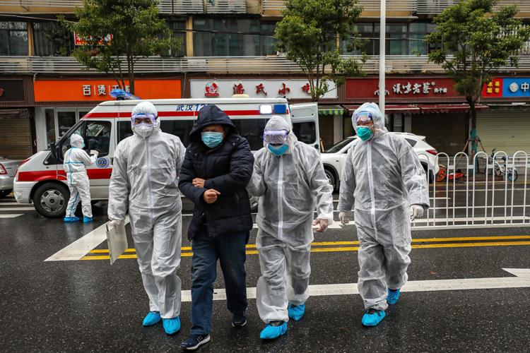 Các nhân viên y tế Trung Quốc hỗ trợ bệnh nhân tại Vũ Hán ngày 27/1. Ảnh: AP.