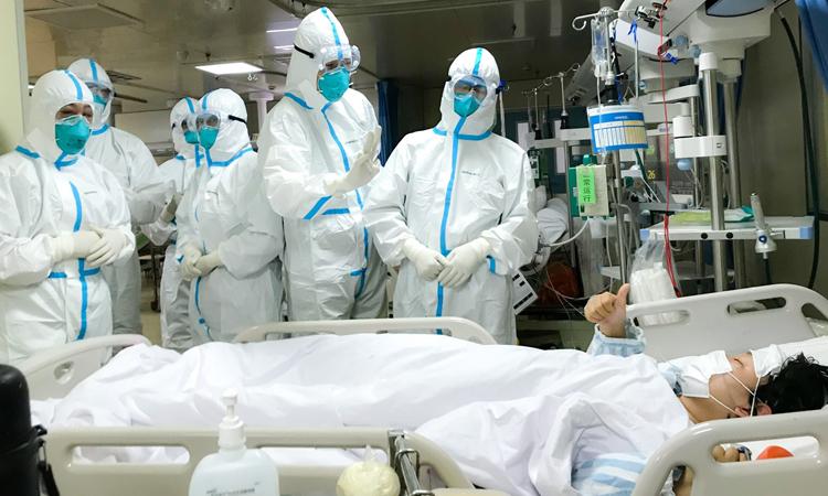 Các bác sĩ ở Vũ Hán trao đổi với một bệnh nhân nhiễm nCoV đang nằm trên giường bệnh hôm 1/2. Ảnh: Xinhua.