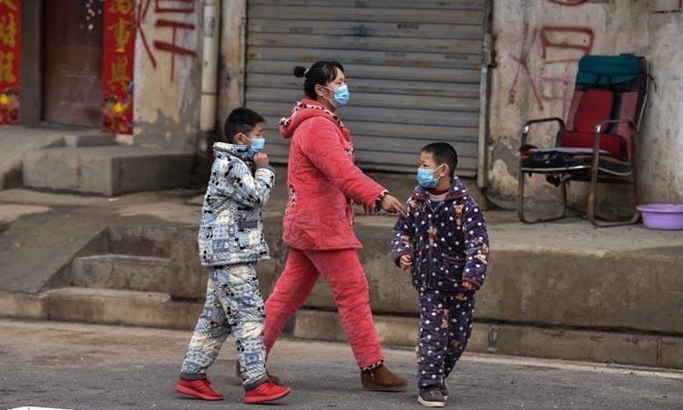 Một gia đình ở Vũ Hán đeo khẩu trang khi đi bộ trên đường phố hôm 27/1. Ảnh: AFP.
