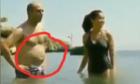 Người đàn ông khổ sở hóp bụng trước người đẹp bikini