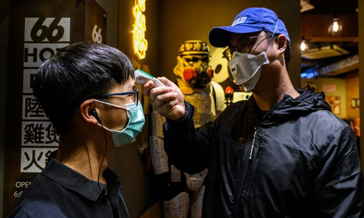 Nhân viên đo thân nhiệt cho khách đến quán lẩu 66 tại khu phố Mongkok. Ảnh: AFP.