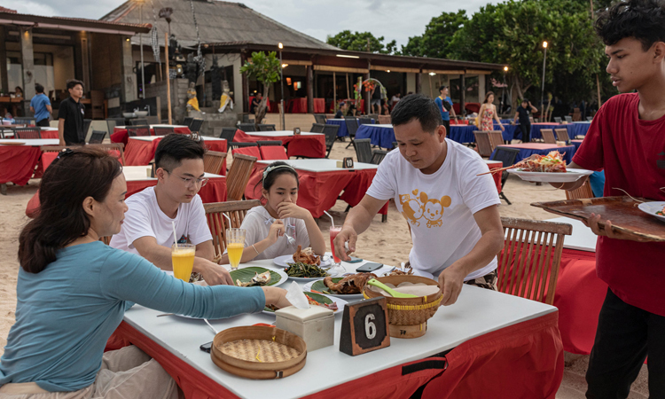 Chai Yin (trái) cùng gia đình đến từ thành phố Thâm Quyến, Trung Quốc ăn trưa trên bãi biển ở Bali. Ảnh: NY Times.