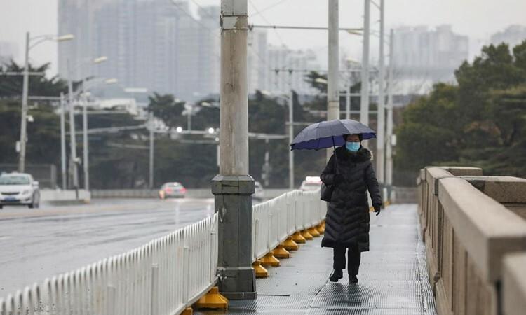 Người phụ nữ đeo khẩu trang đi bộ trên cầu dưới trời mua ở Vũ Hán, tỉnh Hồ Bắc hôm 25/1. Ảnh: AP.