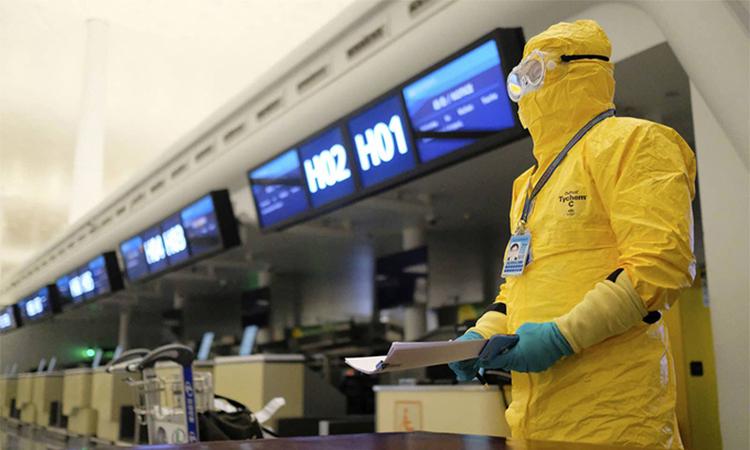 Một nhân viên ở sân bay quốc tế Thiên Hà Vũ Hán mặc đồ bảo hộ, chuẩn bị giấy tờ cho chuyến bay sơ tán các công dân Liên minh châu Âu (EU) hôm 1/2. Ảnh: AP.