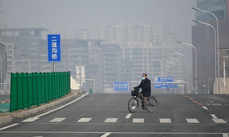 Người đàn ông đeo khẩu trang đạp xe trên phố không bóng người ở Bắc Kinh hôm 12/2. Ảnh: Washington Post.