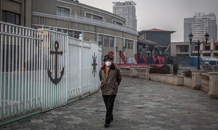 Người đàn ông đeo khẩu trang đi bộ bên ngoài trung tâm mua sắm Solana vắng tanh ở Bắc Kinh hôm 12/2. Ảnh: Washington Post.