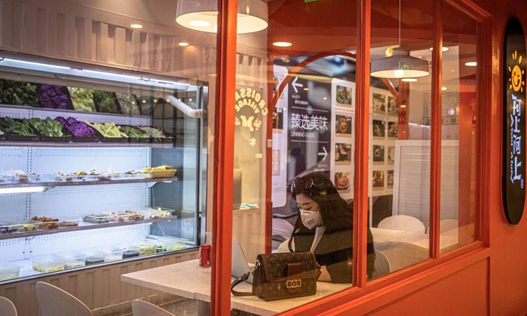Người phụ nữ đeo khẩu trang ngồi một mình trong quán cà phê ở trung tâm thương mại  Solana, Bắc Kinh hôm 12/2. Ảnh: Washington Post.