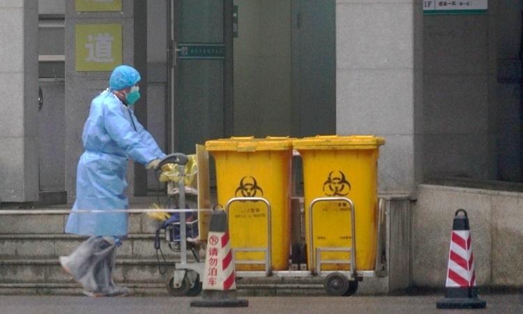 Công nhân thu gom rác thải y tế tại một trung tâm điều trị bệnh nhân nhiễm nCoV ở Vũ Hán hôm 22/1. Ảnh: AP.