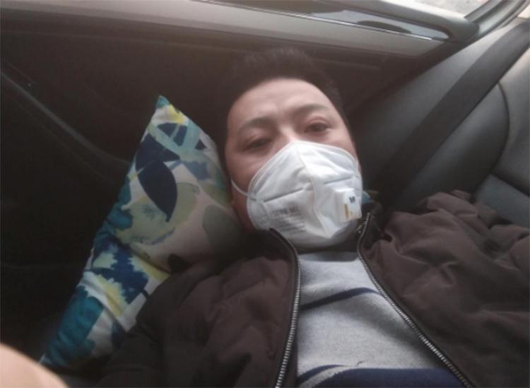 Tian Bing nằm ở ghế sau của xe tại trạm dịch vụ đường cao tốc ở thị xã Nghi Chinh, tỉnh Giang Tô hôm 12/2. Ảnh: Reuters