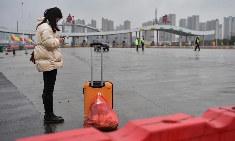 Một nữ y tá đang chờ xe đưa trở lại làm việc tại bệnh viện ở Vũ Hán ngày 25/1. Ảnh: AFP.