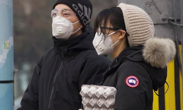 Một cặp đôi đứng chờ đèn đỏ ở Bắc Kinh hôm 13/2. Ảnh: AP.
