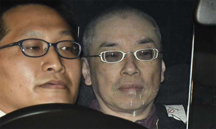 Kaoru Hasegawa (phải) bị đưa đến đồn cảnh sát sau khi bị bắt hôm 28/4. Ảnh: Kyodo