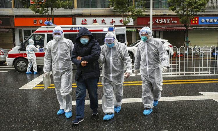 Nhân viên y tế mặc đồ bảo hộ giúp đỡ bệnh nhân ở Vũ Hán. Ảnh: AP.