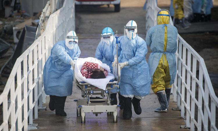 Nhân viên y tế đưa bệnh nhân vào bệnh viện dã chiến Hỏa Thần Sơn ở Vũ Hán. Ảnh:XIAO YIJIU / AP