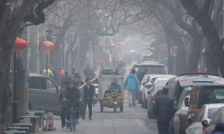 Người dân đi lại trong làn khói mù ô nhiễm tạimộtphố cổ ở Bắc Kinh ngày 2/3/2019. Ảnh: Reuters.